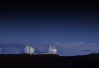 The two Keck telescopes peering out into the night sky, while darkness falls upon them. The summir of Mauna Kea sits so high that the clouds are almost always beneath the Keck telescopes. - Rick Peterson