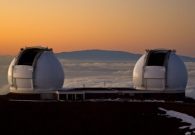 The sun sets on Mauna Kea as the twin Kecks prepare for observing. Haleakala lies in the distance. - Pablo McLoud